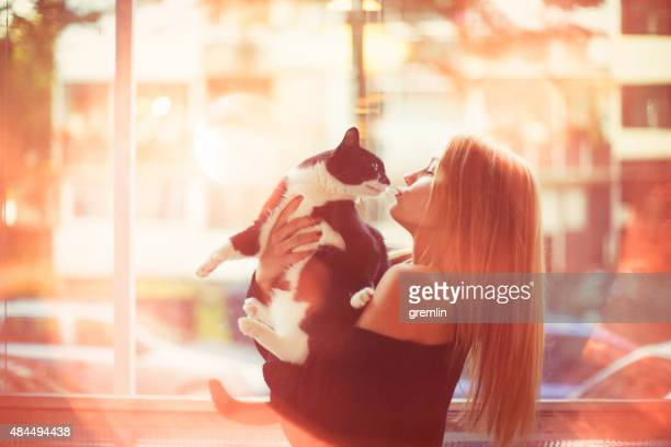 Young woman kissing her cat