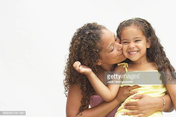 Young woman kissing her daughter