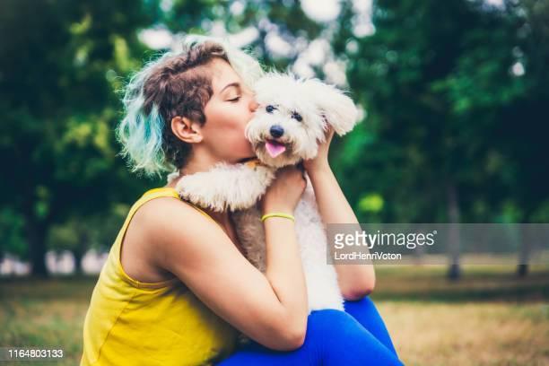 若い女性は屋外で彼女の犬にキスをします。 - 愛玩犬 ストックフォトと画像