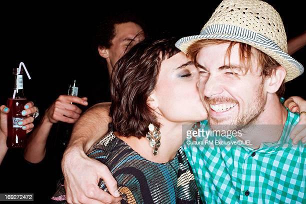 Young woman kissing man at party