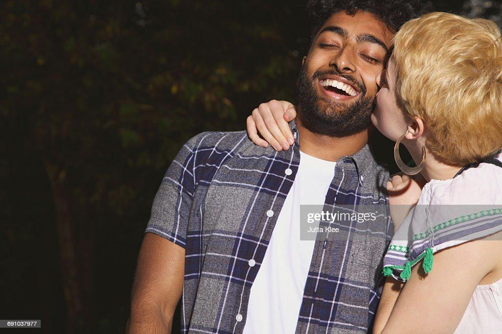 Young woman kissing man at yard : Stock Photo