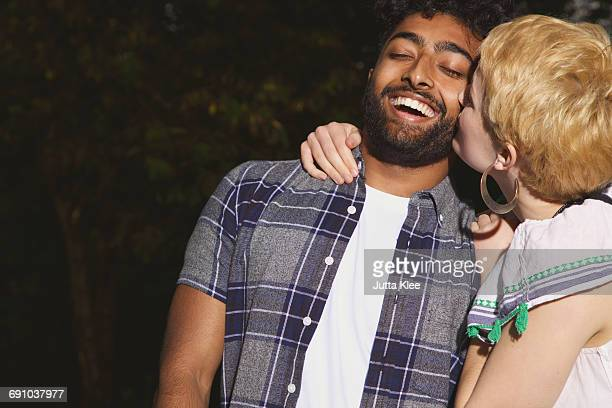 Young woman kissing man at yard