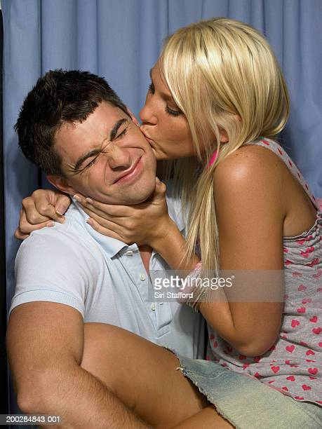 Young woman kissing man in photo booth