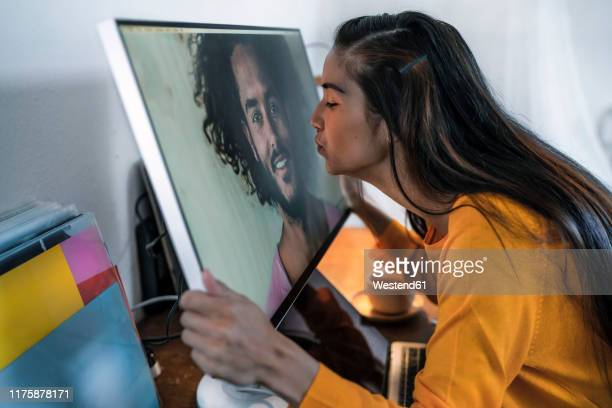 young woman kissing man on computer screen - long distance relationship stock pictures, royalty-free photos & images