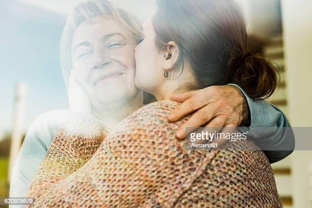 Young woman kissing senior woman behind windowpane