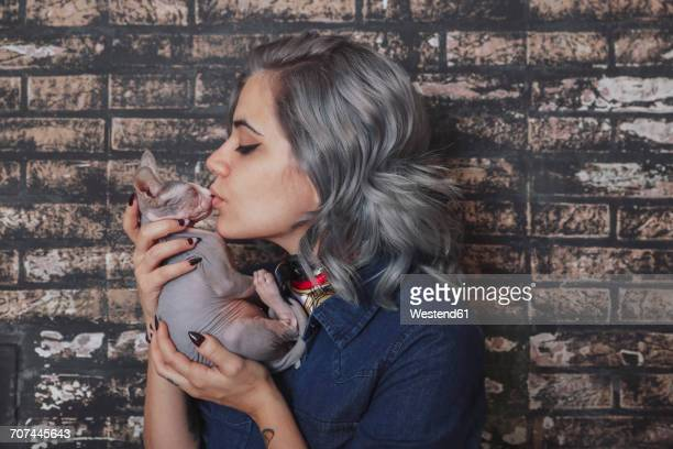 Young woman kissing Sphynx cat