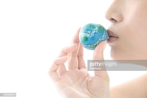 young woman kissing the globe ball,lip close up
