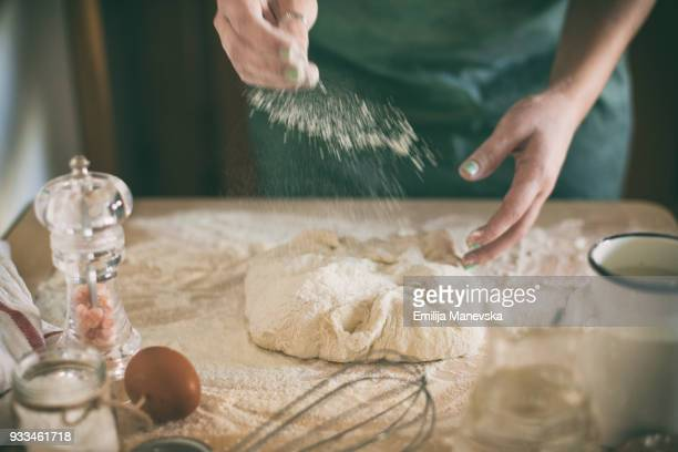 Young woman kneading dough in kitchen