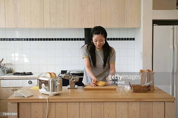 Young woman kneading pasta dough in the kitchen