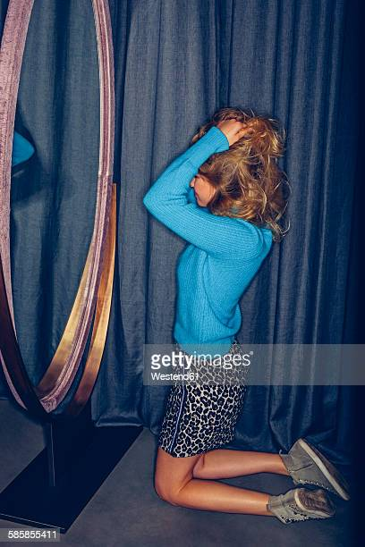 Young woman kneeling in a fitting room