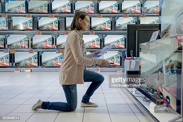 Young woman kneeling in front of flat panel television in electronics store