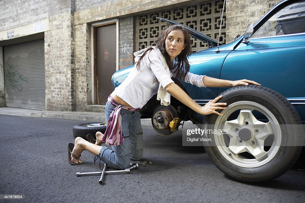 Young Woman Kneeling in the Road Changing a Tyre on a Classic Car : Stock Photo