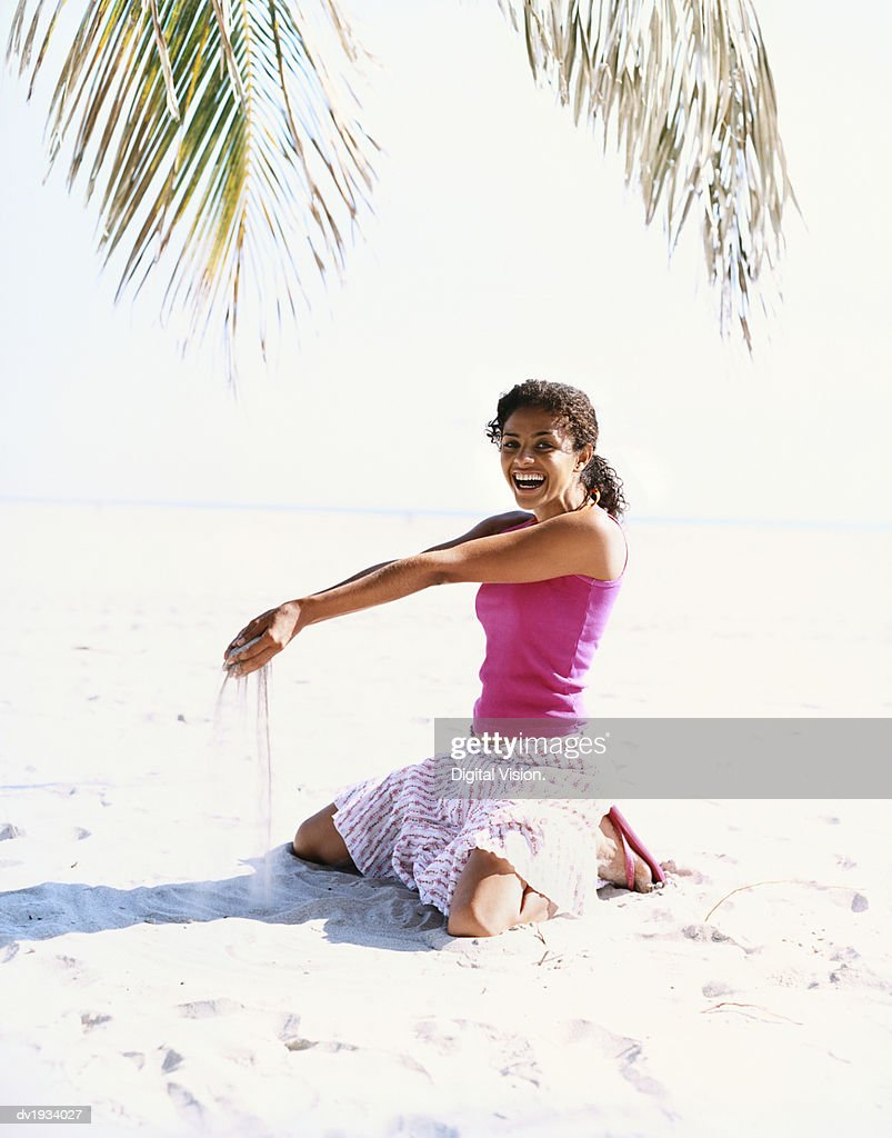 Young Woman Kneeling on a Beach With Sand Pouring From Her Hands : Stock Photo