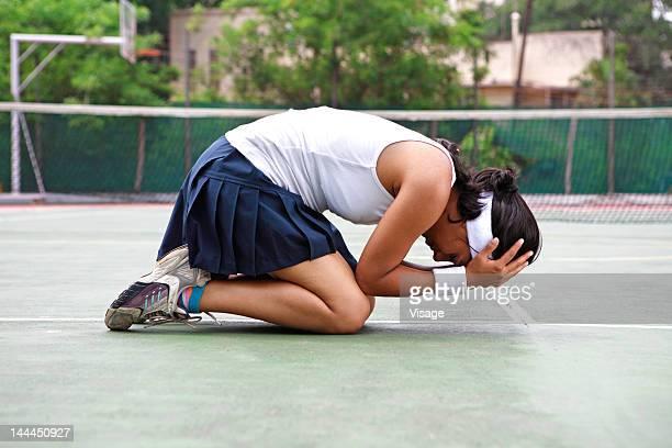 young woman kneeling on a tennis court - niederlage stock-fotos und bilder