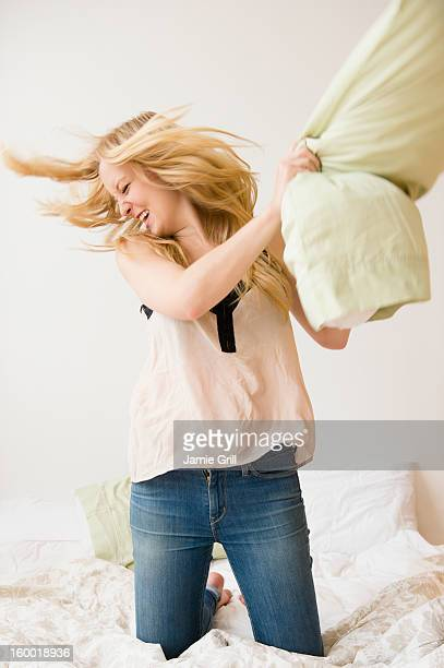 Young woman kneeling on bed and throwing pillow