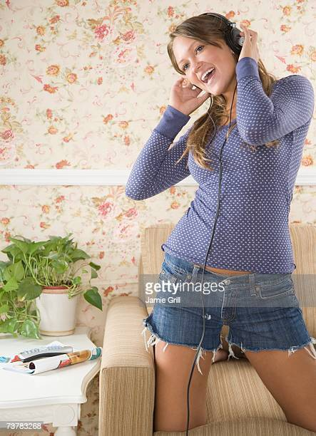 young woman kneeling on sofa and listening to music on headphones - teen mini skirt stock photos and pictures
