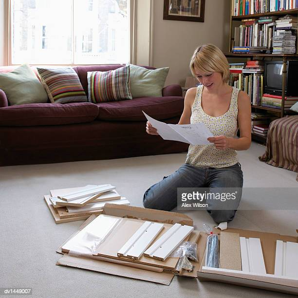 Young Woman Kneeling on the Floor of Her Living Room Reading the Instructions For Assembling Flatpack Furniture