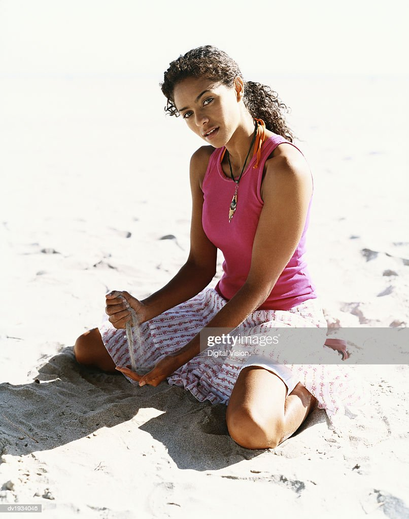 Young Woman Kneels on the Sand, Pouring it Through Her Fingers : Stock Photo