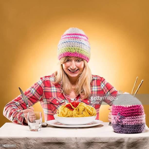 Young woman knitter portrait eating wool spaghetti with winter hats
