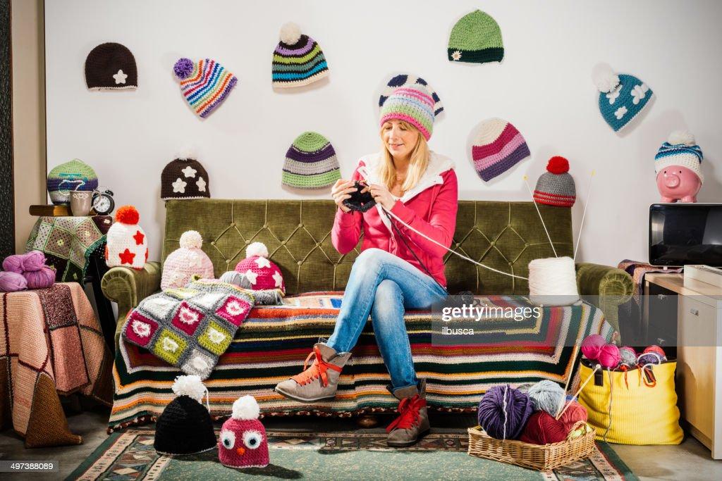 Bild einer strickenden, jungen Frau auf einer couch mit Wintermützen : Stock-Foto