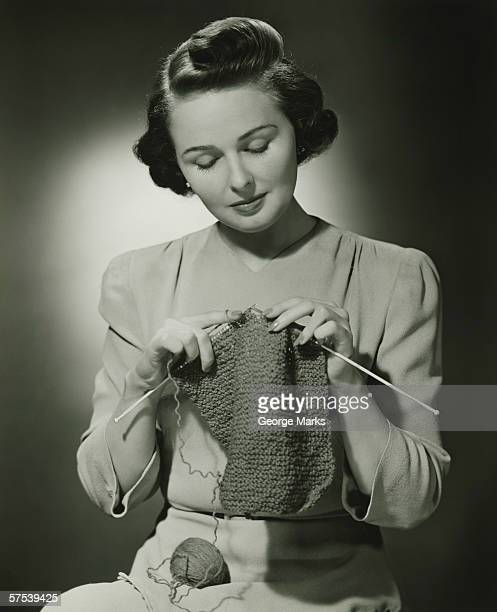 Young woman knitting in studio, (B&W)