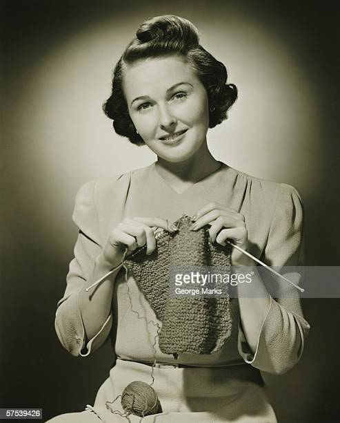 Young woman knitting in studio, (B&W), portrait