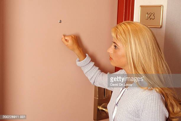 young woman knocking on door, side view - knocking on door stock photos and pictures