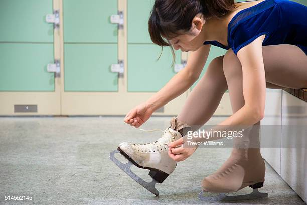 A young woman lacing up her ice skates
