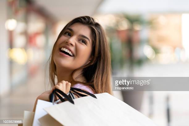 Young woman laughing and holding shopping bags over her shoulder looking away excited