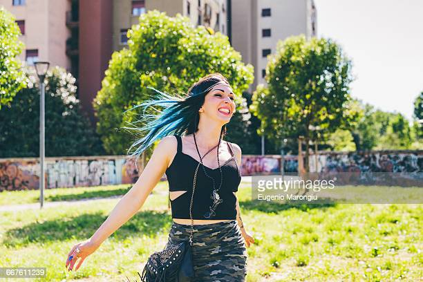 Young woman laughing and running in urban park
