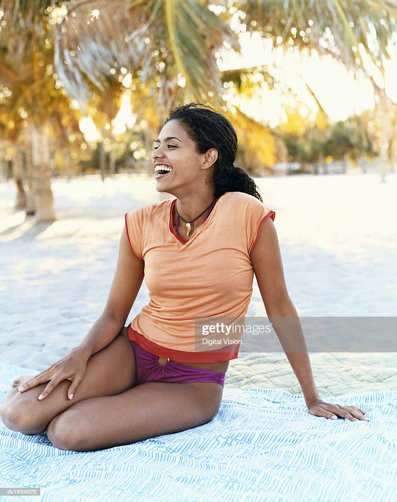 Young Woman Laughing and Sitting on a Beach : Stock Photo