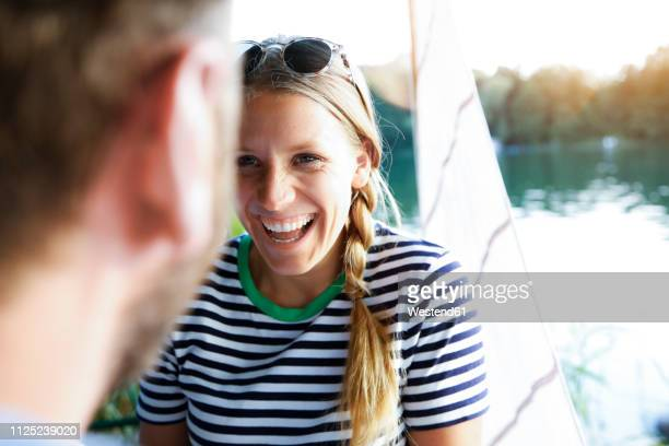 young woman laughing at man at a lake next to sailing boat - heterosexual couple stock pictures, royalty-free photos & images