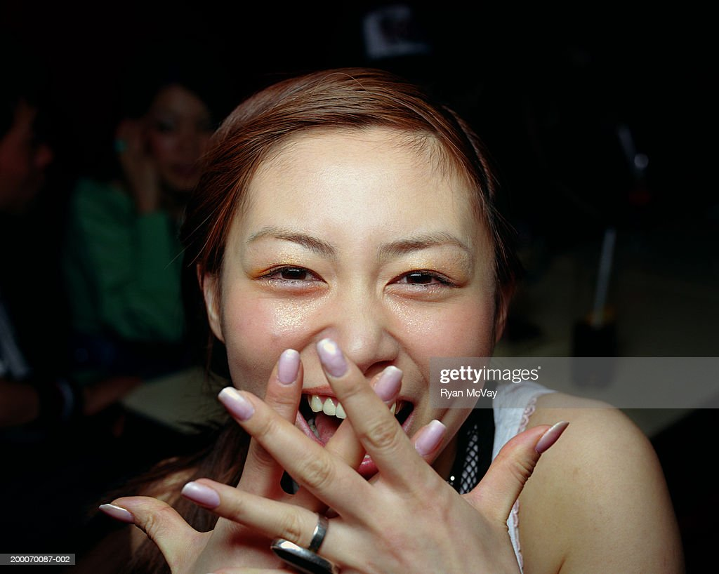 Young woman laughing, covering mouth with hands, close-up : Stock Photo