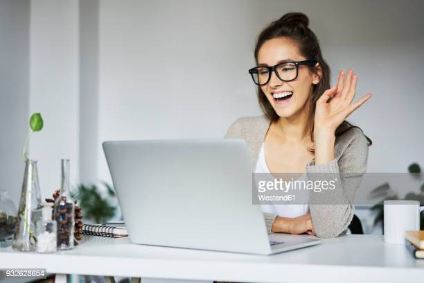 Young woman laughing during video chat at desk