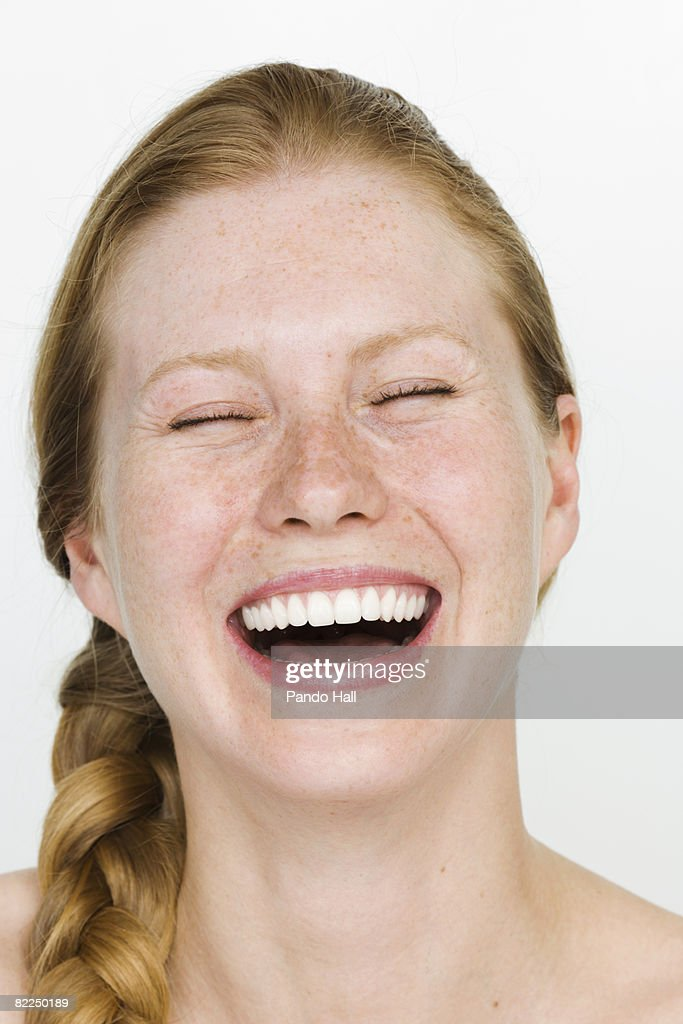 Young woman laughing, eyes closed, portrait : Stock Photo