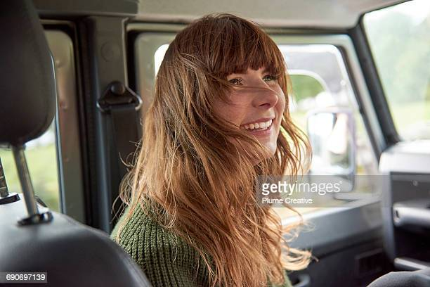 Young woman laughing in car