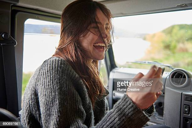 Young woman laughing in passenger seat of car