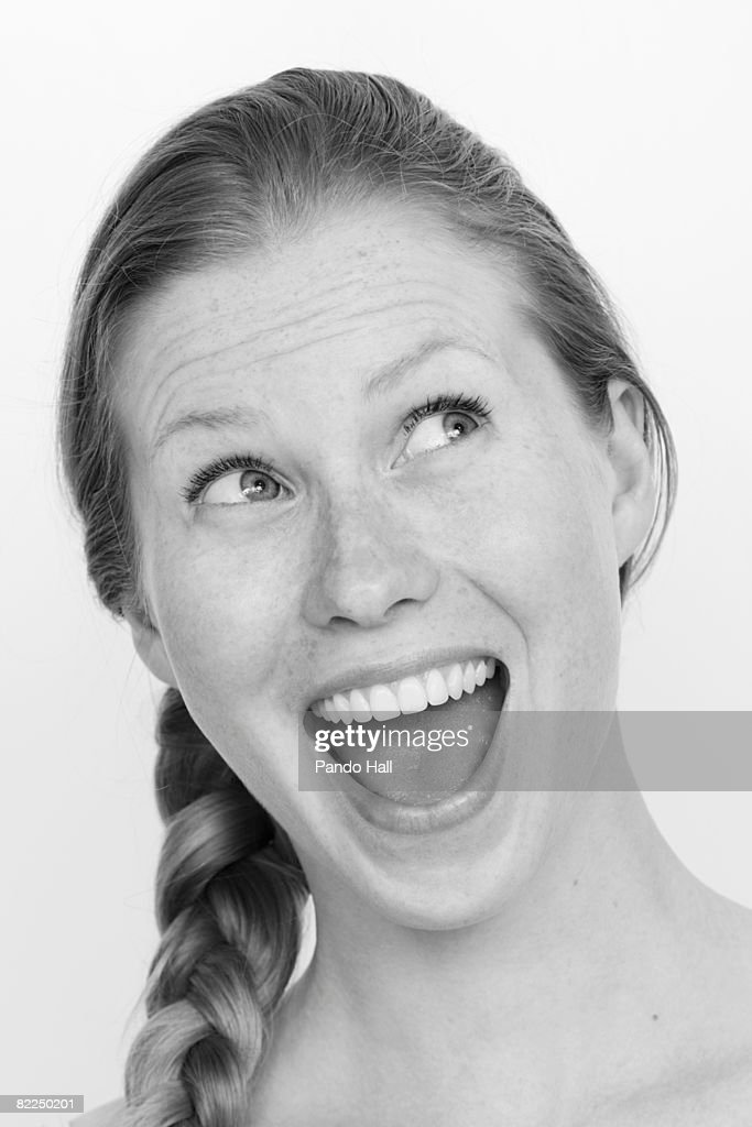 Young woman laughing, looking up, portrait : Stock Photo