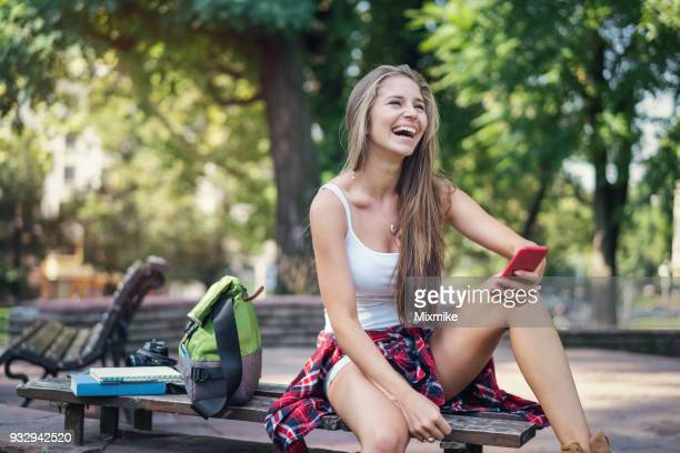 Young woman laughing loudly and chatting online