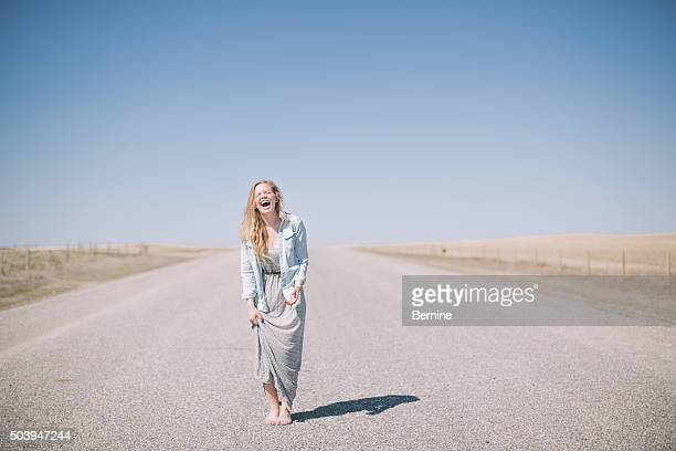 young woman laughing on road - long dress stock pictures, royalty-free photos & images