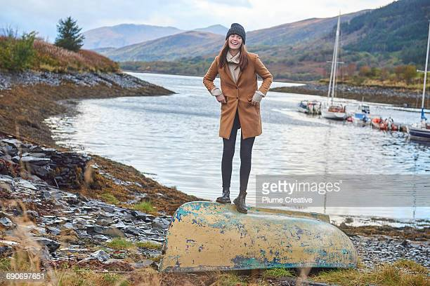 young woman laughing standing by a loch - coat ストックフォトと画像