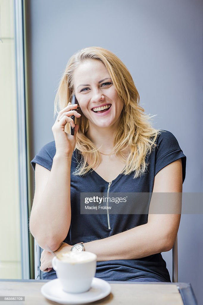 Young woman laughing when talking on the phone : Stock Photo