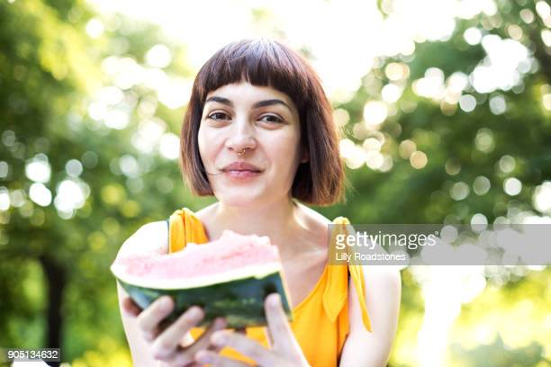Young woman laughing while eating water melon