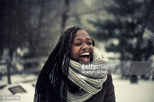 Young woman laughing while it's snowing outside