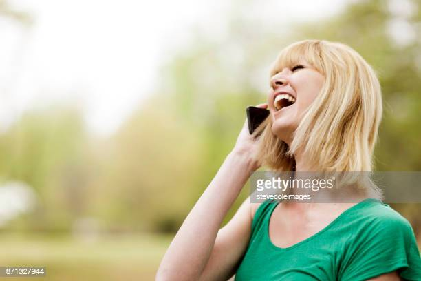 Young woman laughing while on mobile phone.