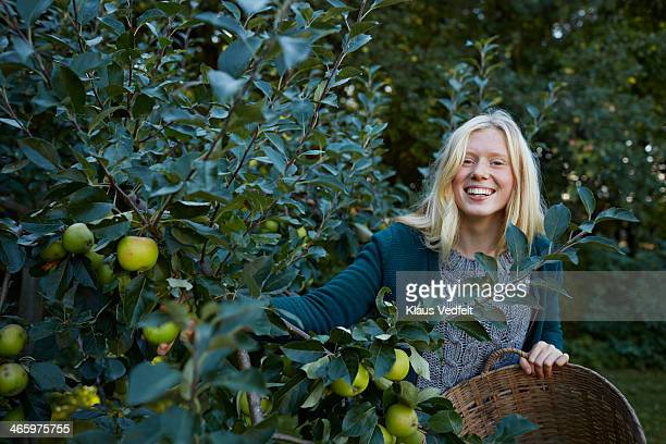 Young woman laughing while picking apples