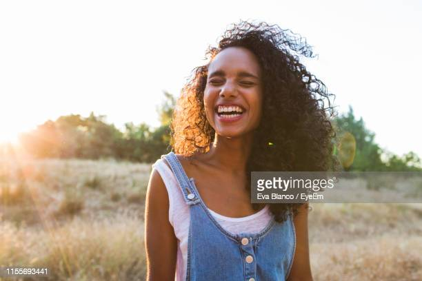young woman laughing while standing by plants against sky - cabelo encaracolado imagens e fotografias de stock