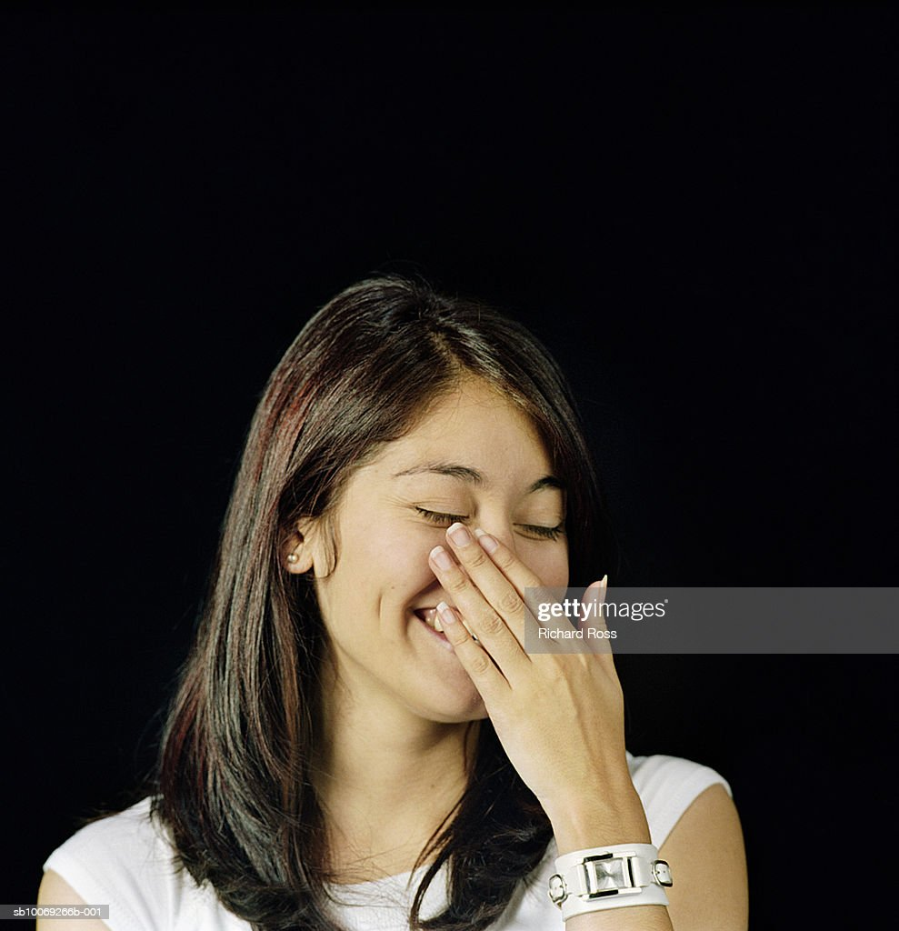 Young woman laughing with hand on mouth, studio shot : Stockfoto