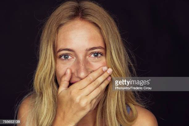 young woman laughing with hand over mouth - surprise stock pictures, royalty-free photos & images