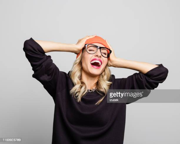 young woman laughing with hands in head - retrato formal imagens e fotografias de stock